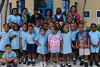 Students, teachers and parents of St George's Pre-school with Principal Ms Magdelena Fernandes (third from left) and the Department of Immigration's Training and Development Manager Ms Jenifer Gager-Sterling (right) outside the Department's headquarters.
